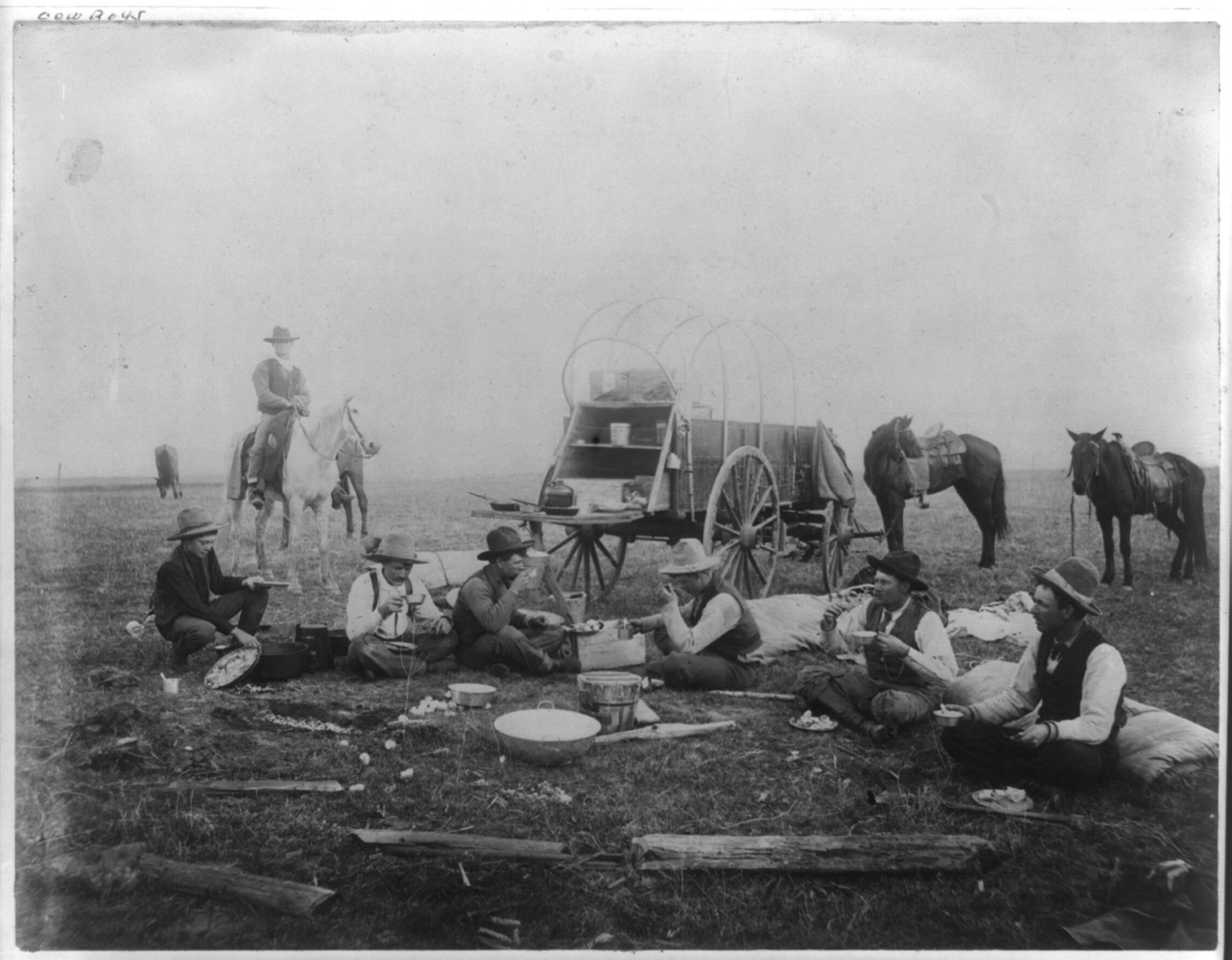 Cowboys eating out on the range, chuck wagon in background